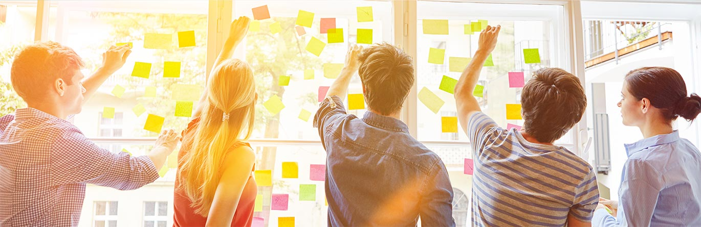people in workshop putting postit notes on window